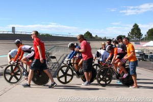 Riders and their handlers roll to a keirin start